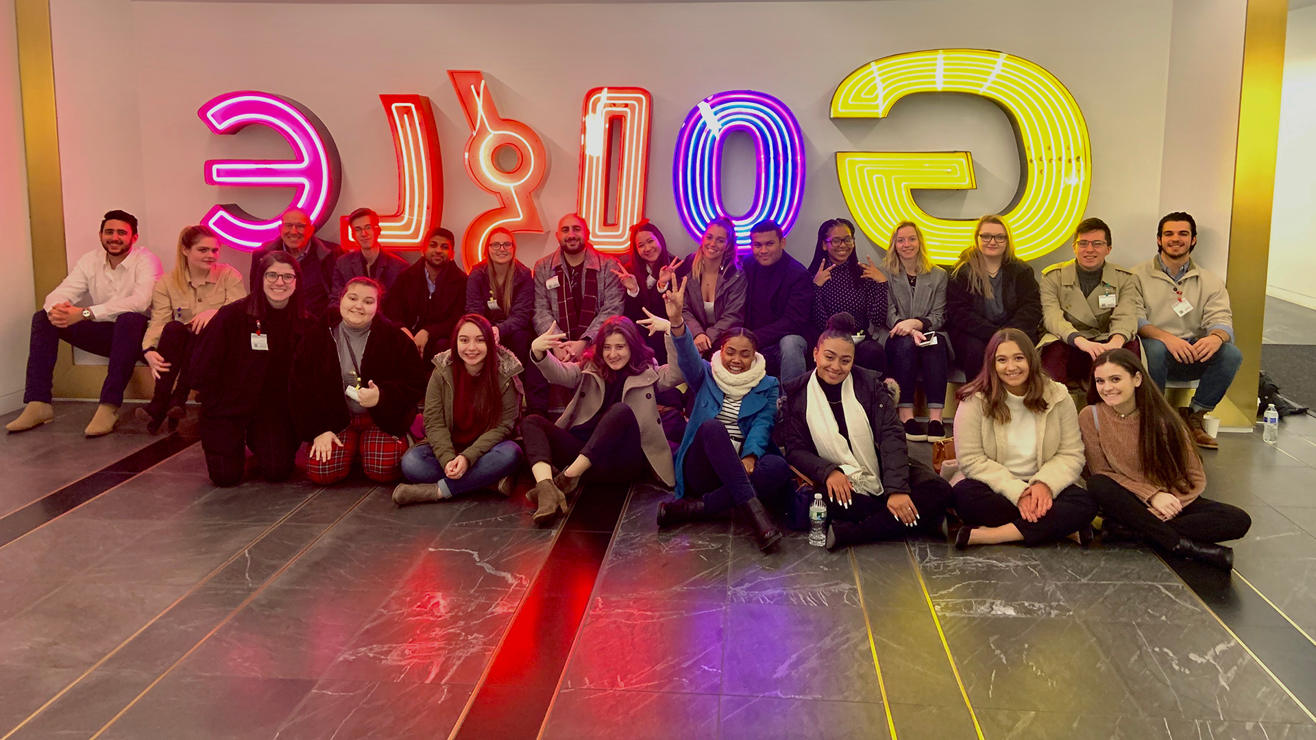 Advertising students in front of Google neon sign