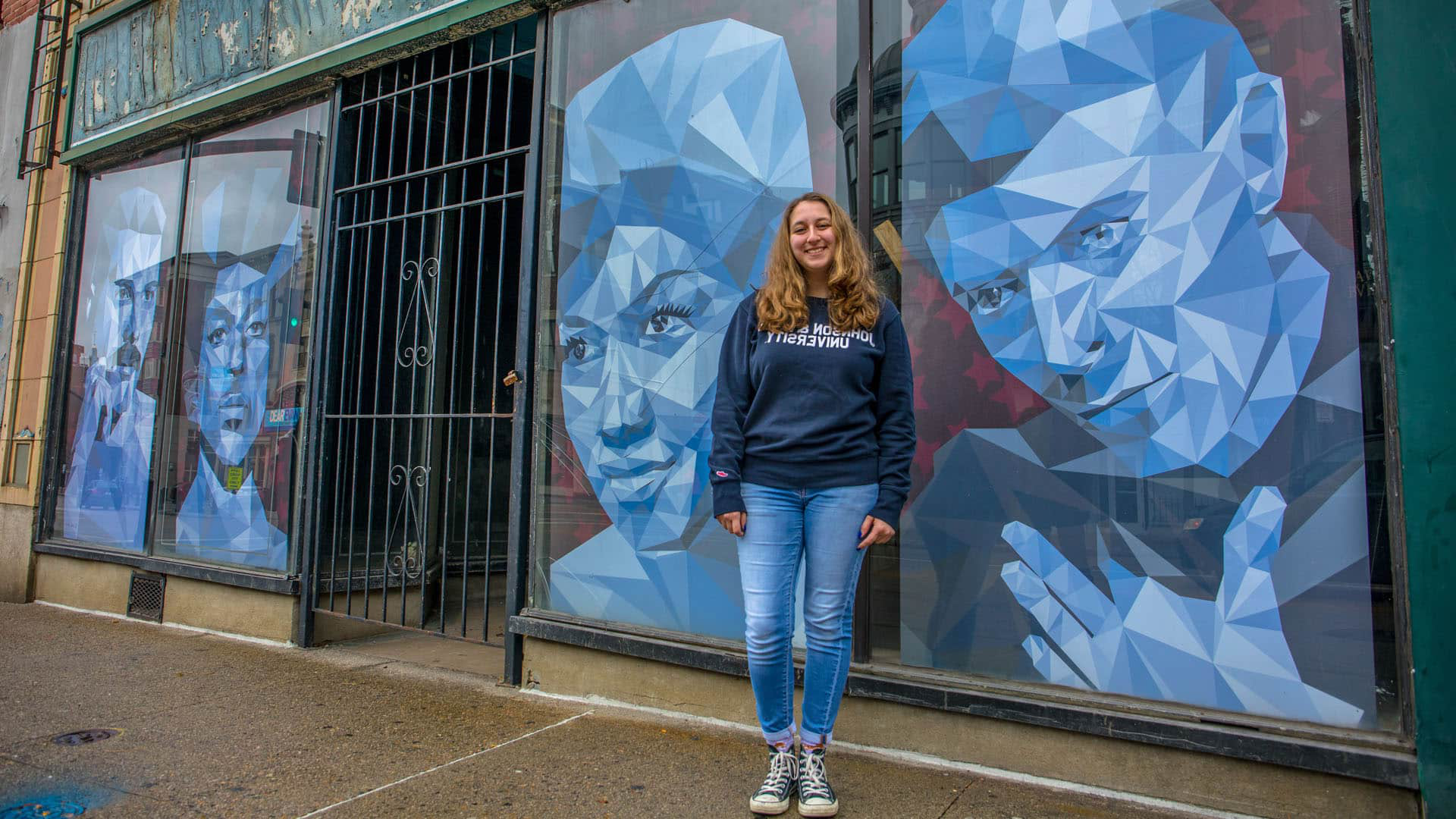 Kristina Faiola stands in front of her designs for the Axelrod Music windows.